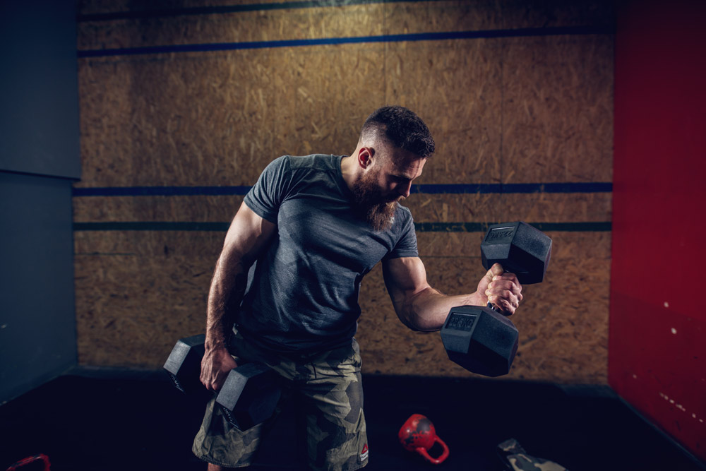 Canva---Portrait-view-of-young-bearded-focused-strong-muscular-shape-bodybuilder-man-doing-biceps-exercises-with-heavy-dumbbells-in-hands-at-the-gym